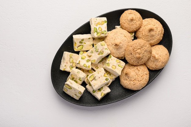 Nougat and almond cookies on a dark plate against a light background.