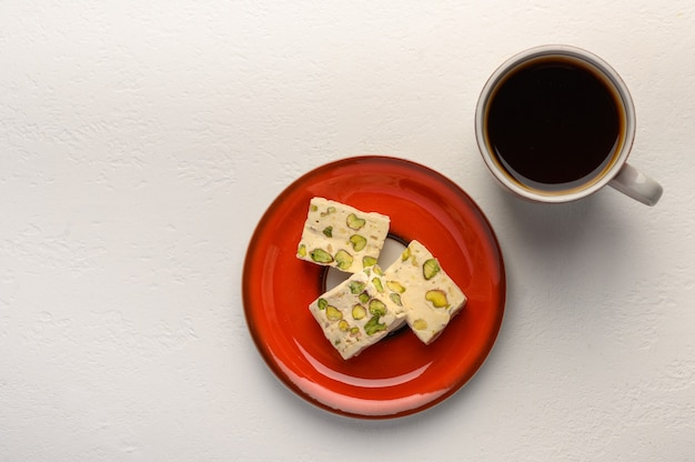 Nougat on a plate and a cup of tea on light background. selective focus.