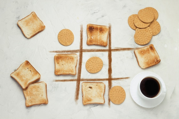 Noughts and crosses choice game competition cookie and square toasted toast, cup with black coffee, white stone background flat lay, top view
