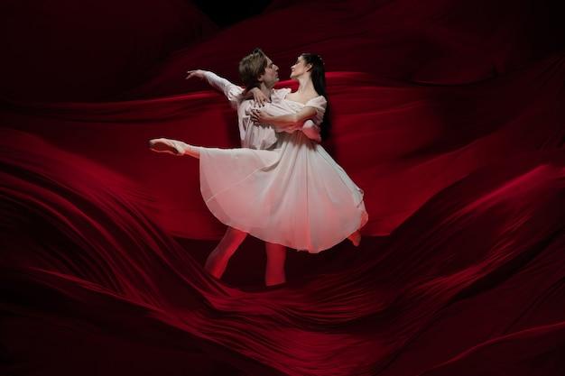 Romanzo. giovani e aggraziati ballerini sulla parete di stoffa rossa in azione classica. arte, movimento, azione, flessibilità, concetto di ispirazione. coppia caucasica flessibile con onde rosse fluttuanti.