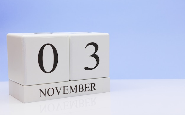 November 03st. day 3 of month, daily calendar on white table with reflection