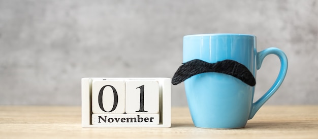 November 1 calendar, blue coffee cup or tea mug and black mustache decor on table. men day, happy father day and hello november concept