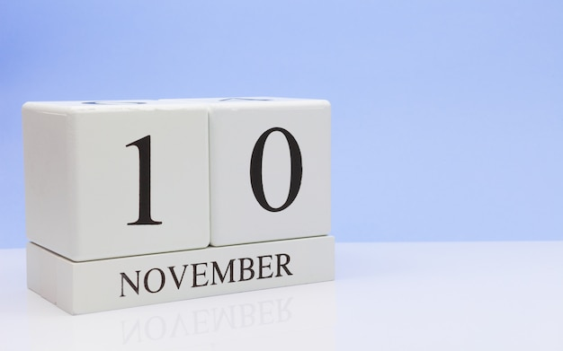 November 10st. day 10 of month, daily calendar on white table with reflection, with light blue background.