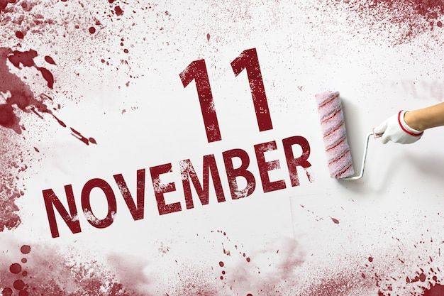 11월 11일 . 매월 11일, 달력 날짜. 손은 빨간색 페인트로 된 롤러를 잡고 흰색 배경에 달력 날짜를 씁니다. 가을 달, 올해 개념의 날.