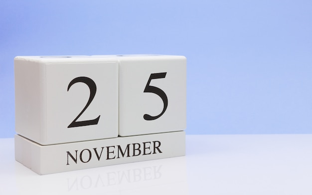 November 25st. day 25 of month, daily calendar on white table with reflection