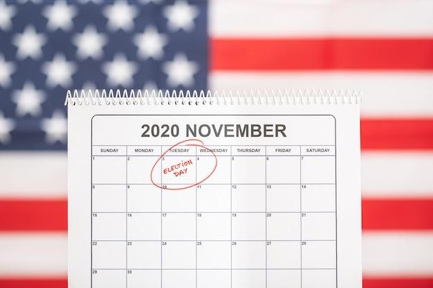 3 ноября 2020 года концепция дня выборов. настольный календарь с 3 ноября, отмеченным красным, и флагом сша на заднем плане