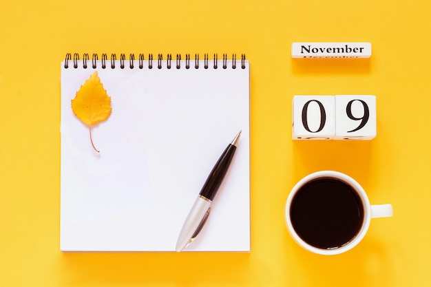 November 9 cup of coffee, notepad with pen and yellow leaf on yellow background