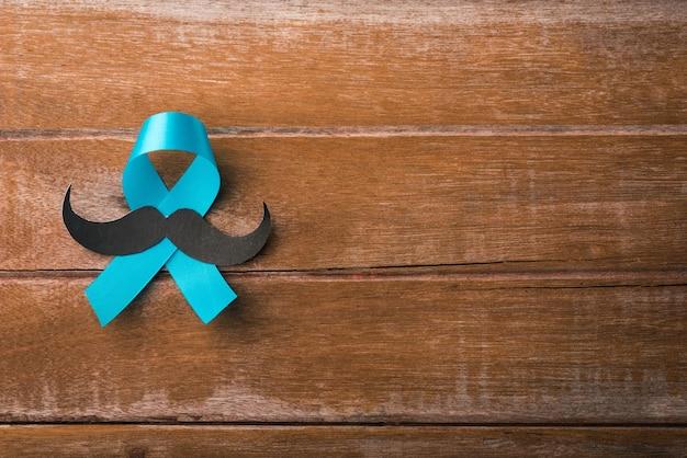 11月の青、木製の背景に男性の口ひげを生やした水色のリボン、男性の健康意識、前立腺癌の意識