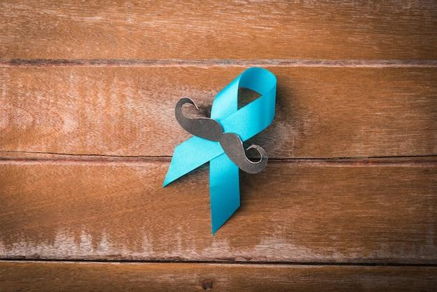 Ноябрьский синий, голубая лента с мужскими усами на деревянном фоне, осведомленность о здоровье мужчин, осведомленность о раке простаты