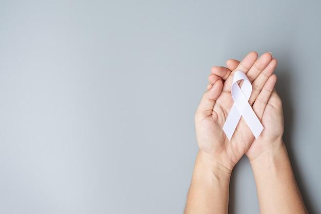 Ноябрь месяц осведомленности о раке легких, день демократии и международного мира. мужчина держит белую ленту на сером фоне