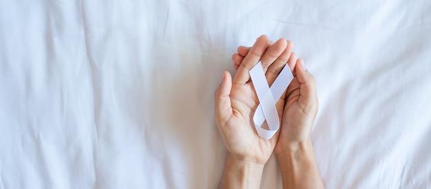 Ноябрь месяц осведомленности о раке легких, день демократии и международного мира. мужчина держит белую ленту на белом фоне