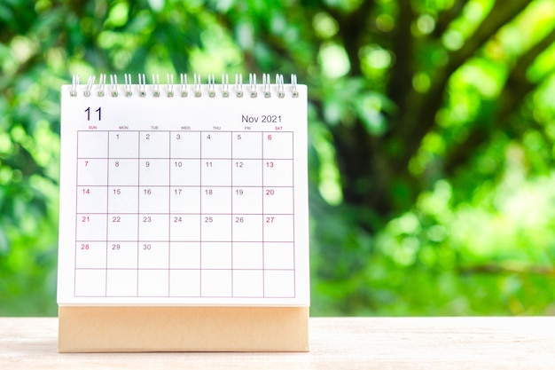 11월, 주최자를 위한 캘린더 데스크 2021은 녹색 자연 배경을 가진 나무 테이블에 대한 계획 및 알림을 제공합니다.