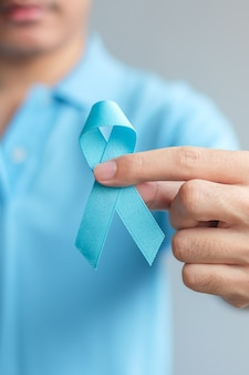 November prostate cancer awareness month, man in blue shirt with hand holding blue ribbon for supporting people living and illness. healthcare, international men, father and world cancer day concept