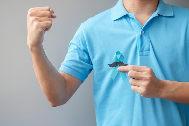 Ноябрь месяц осведомленности о раке простаты, мужчина держит синюю ленту с усами для поддержки людей, живущих и больных. здравоохранение, международные мужчины, отец и всемирный день борьбы против рака