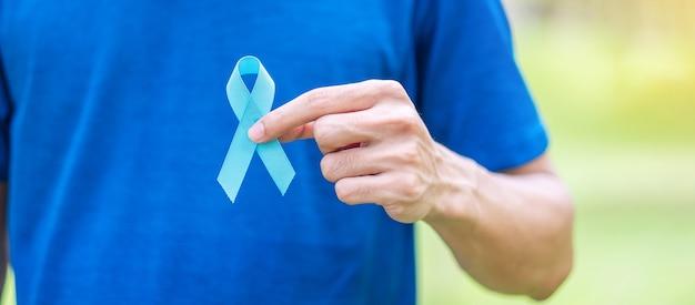 11月の前立腺がん啓発月間、生きている人々と病気をサポートするための青いリボンを持っている手を持つ青いtシャツの男。ヘルスケア、国際的な男性、父と世界の癌デーの概念