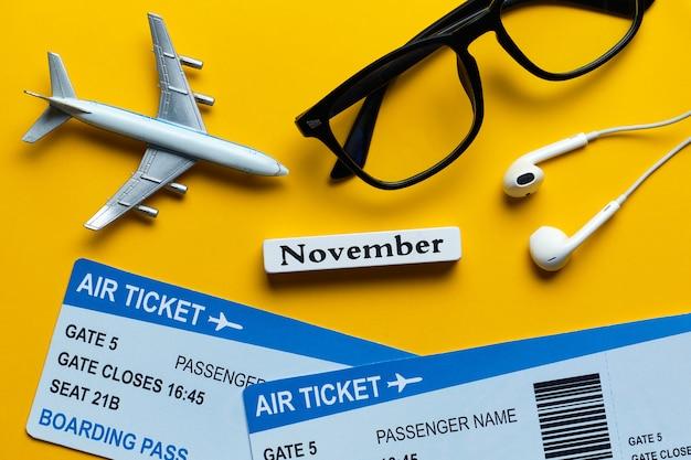 黄色の背景にチケットと飛行機モデルの横にある11月の休暇の概念。