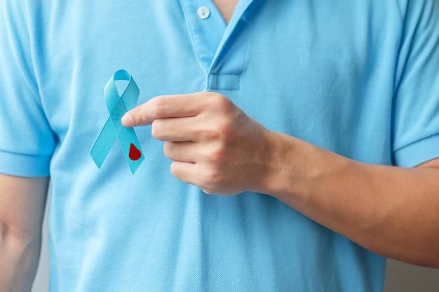 11월 세계 당뇨병의 날 인식의 달, 사람들의 생활, 예방 및 질병을 지원하기 위해 혈액 방울 모양으로 밝은 파란색 리본을 들고 있는 남자. 건강 관리, 전립선 암의 날 개념