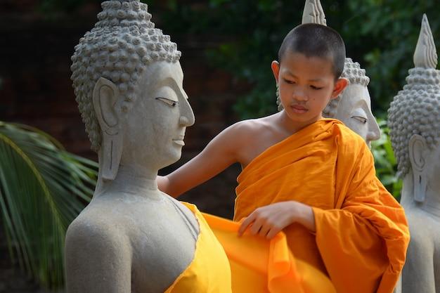 Novice covering the robe of the buddha statue, at wat yai chaimongkol, ayutthaya, thailand, may 21, 2021.