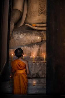 The novice is looking at the large buddha image in the church to pray for the respect of religion.