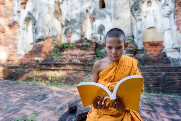 Novice monk reading outdoors, sitting outside monastery, thailand