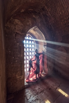 Novice monk standing in ancient temple