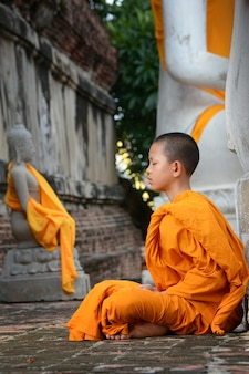 Novice practicing meditation at wat yai chaimongkol, ayutthaya, thailand, may 21, 2021.