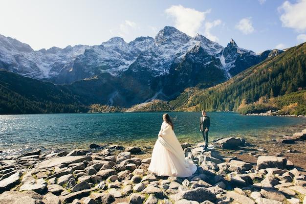 Novios en el lago de montaña al amanecer