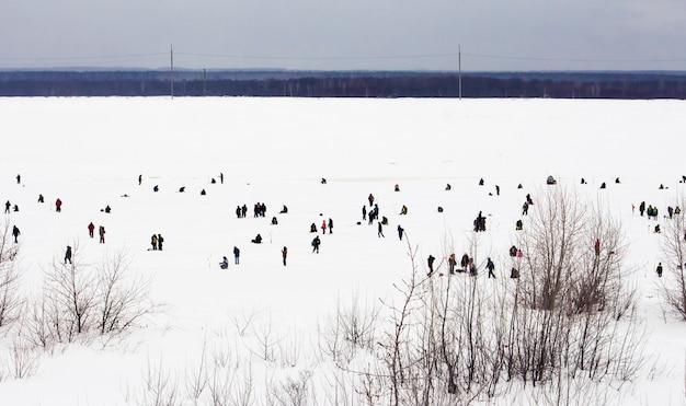 Novocheboksarsk, 러시아 -2 월 27, 2021 : Rybak Rybak 축제, 얼어 붙은 강에서 낚시. 프리미엄 사진