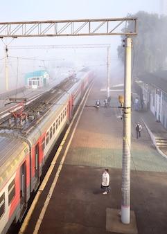 ノボシビルスク、シベリア、ロシア-08.15.2021:ロシア鉄道の郊外列車の車の駅のプラットフォーム上の人々