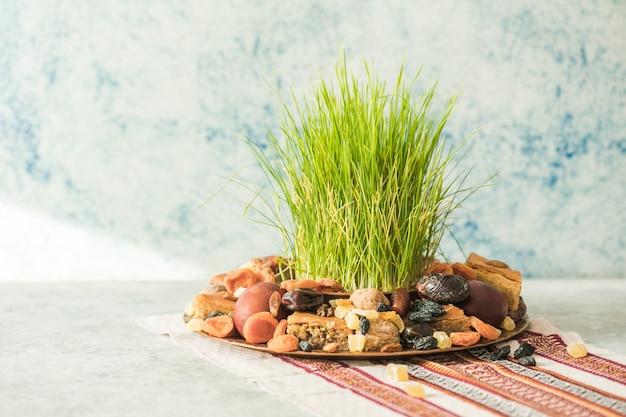 Традиционный поднос новруз с семени или сабзи зеленой травы пшеницы, сладостями и пахлавой сухофруктов на белом фоне. весеннее равноденствие, азербайджан copy space Premium Фотографии