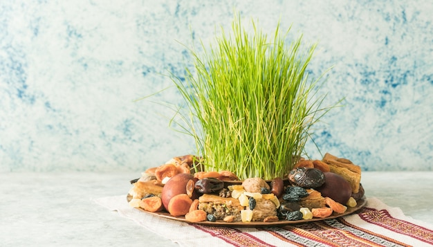 Традиционный поднос новруз с семени или сабзи зеленой травы пшеницы, сладостями и пахлавой сухофруктов на белом фоне. весеннее равноденствие, азербайджан copy space