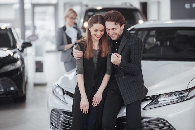 今彼女の夢が叶います。若い魅力的な所有者に新しい車の鍵を与える車のセールスマン