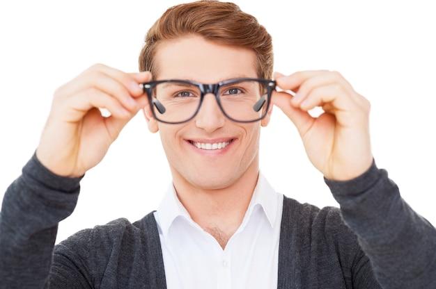 今、私はあなたをよく見ることができます。白に孤立して立っている間眼鏡を保持し、それらを通して見るハンサムな若い男