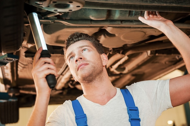 Now i see the problem. low angle view of confident young man in uniform holding lamp while standing underneath a car in workshop