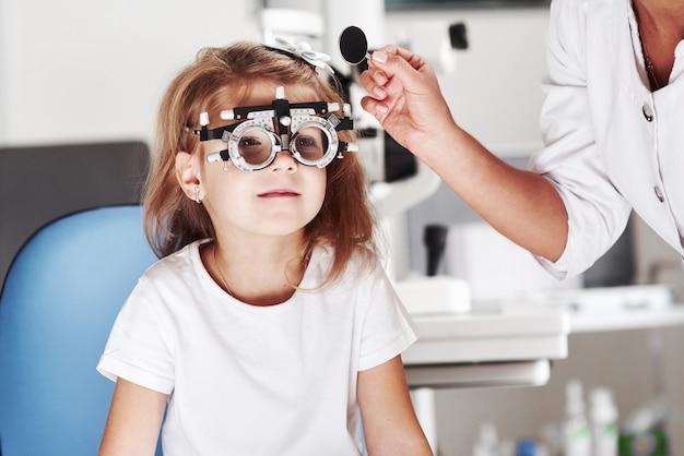 今、私は片目を閉じます。医者は小さな女の子の視力をチェックし、フォロプターを調整します。