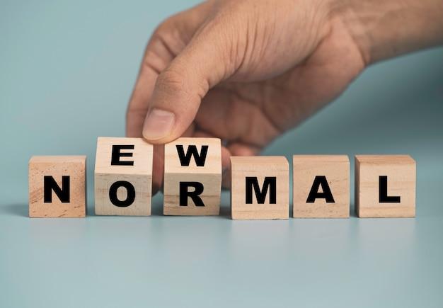 現在、青い背景の木製の立方体ブロックの通常の文言の印刷画面、covid-19パンデミック感染の概念によるビジネスとライフスタイルの変化。