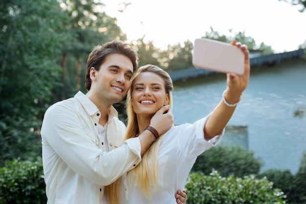 今笑顔。夫と一緒に自分撮りをしながらスマートフォンを抱きしめるうれしそうな幸せな女性