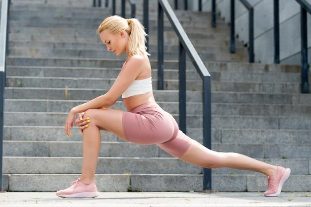 이제 몇 가지 스트레칭 운동 야외에서 다리를 기지개하는 운동 여자 스트레칭 운동