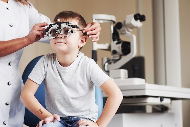 それがどのように見えるか教えてください。医院に座って視力をテストした子供。