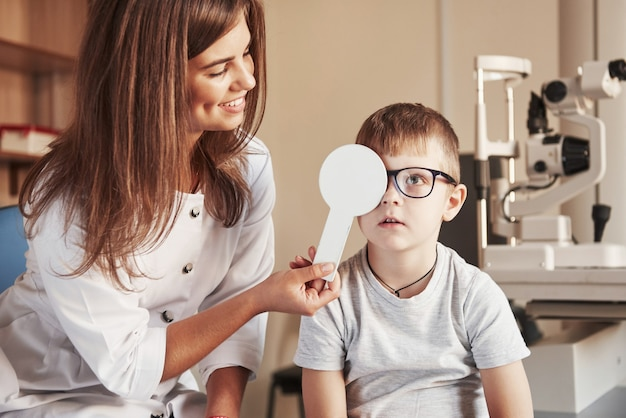 Now tell me what you see. female doctor covers kid eye with medical tool for checking visual acuity.
