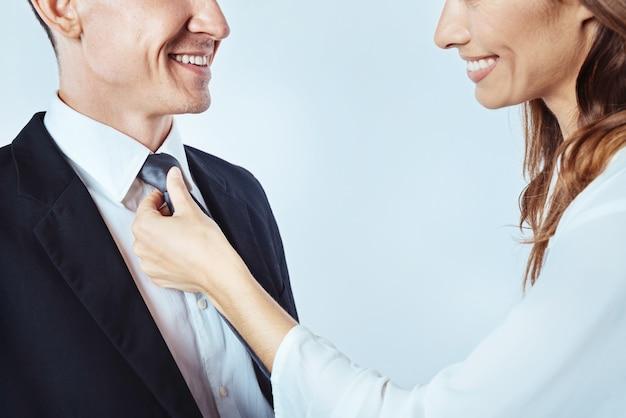 これで準備が整いました。晴れやかな男を見て、背景の上に彼のネクタイを調整しながら笑顔の前向きな女性のクローズアップ。
