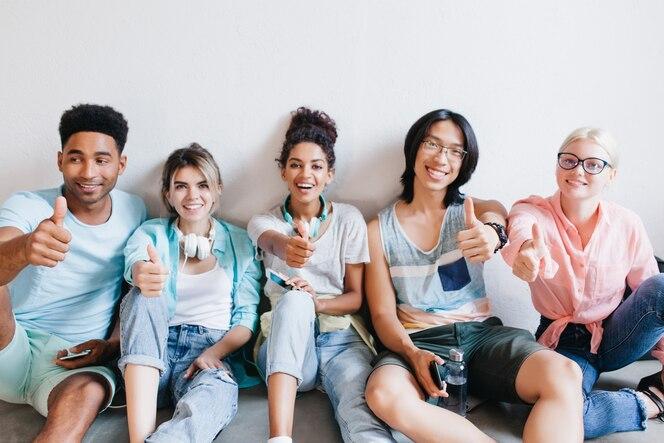 바닥에 앉아 엄지 손가락으로 포즈를 취하는 국제 학생들. 세련된 옷을 입은 행복한 대학 친구들이 수업 후 캠퍼스에서 즐거운 시간을 보냅니다.