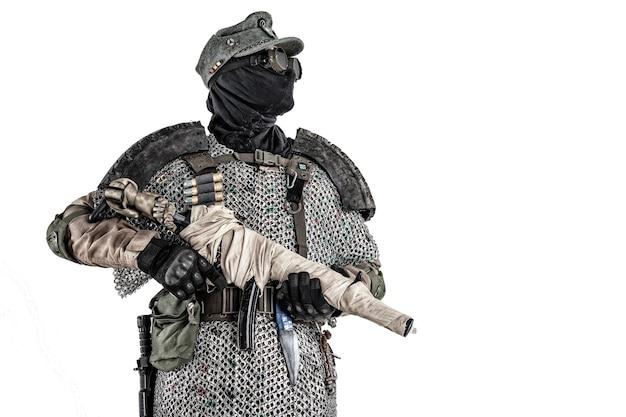 Выживший в ядерном постапокалипсисе, нацистский солдат альтернативной истории или партизан в шерстяной полевой фуражке, маске для лица, очках и доспехах ручной работы, целится из пистолета-пулемета в съемке в фотостудии, изолированной на белом