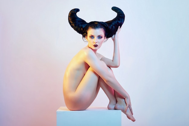 Nude art woman with hair in the form of horns