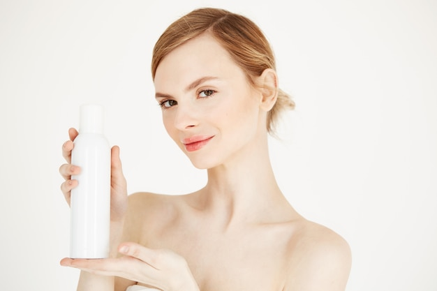 Nude beautiful blonde girl with fresh perfect skin smiling holding cosmetology spray bottle .