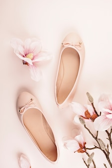 Nude colored ballerina shoes and magnolia flowers.