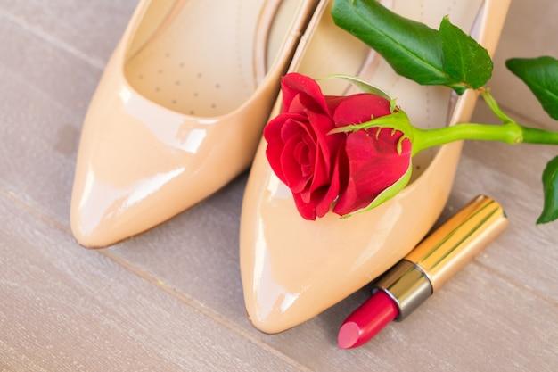 赤いバラのつぼみと口紅のあるヌードカラーのハイヒールの靴の静物