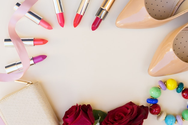 Nude colored high heels shoes with lipsticks, flowers and wallet hero header