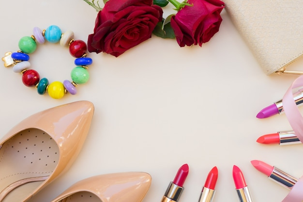 Nude colored high heels shoes with lipsticks and wallet hero header