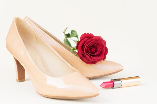 新鮮な赤いバラのつぼみと口紅のあるヌードカラーのハイヒールの静物